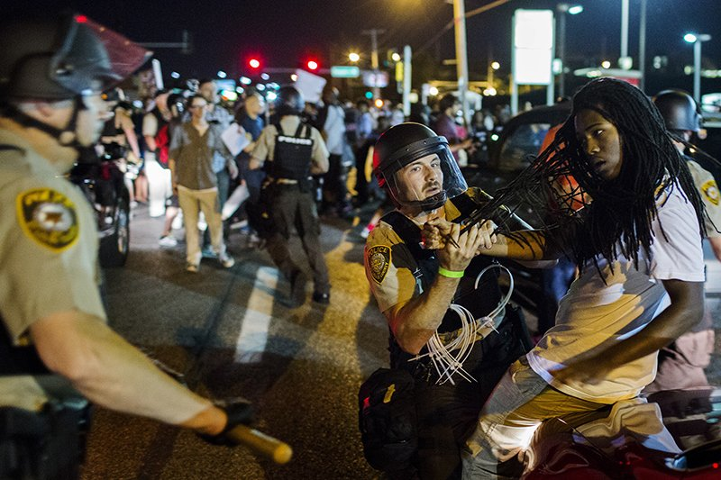 St Louis County police officers hold an anti-police demonstrator in Ferguson, Mo., on August 10, 2015. Police in riot gear clashed with protesters who had gathered in the streets of Ferguson early on Tuesday to mark the anniversary of the police shooting of an unarmed black teen whose death sparked a national outcry over race relations. Photo courtesy of REUTERS/Lucas Jackson *Editors: This photo may only be republished with RNS-POLICE-RELIGION, originally transmitted on August 20, 2015.