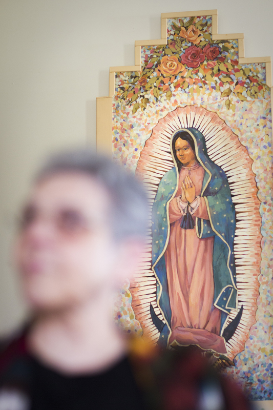 In front of a painting of Our Lady of Guadalupe, Sister Monica sits in her home. She has spent her career ministering to transgendered people. Religion News Service photo by Philip Scott Andrews