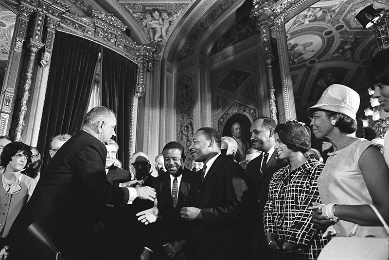 President Lydon B. Johnson and Martin Luther King Jr. shake hands at the signing of the Voting Rights Act of 1965. Photo courtesy of Wikimedia Commons, Public Domain