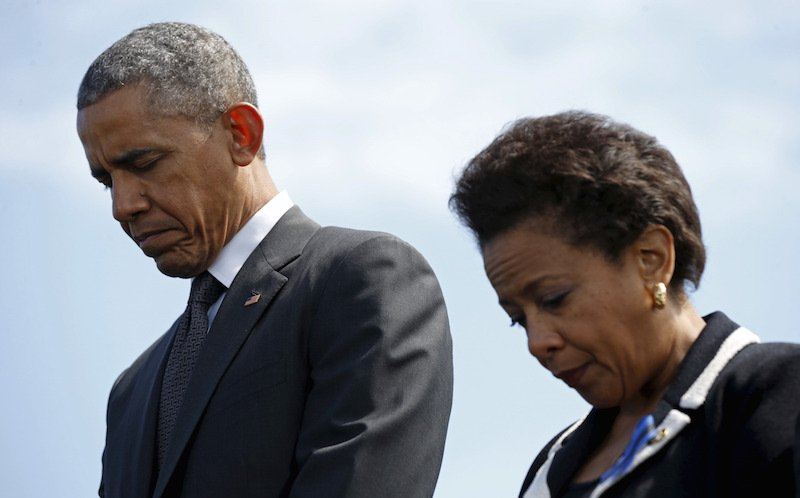 President Barack Obama and Attorney General Loretta Lynch bow their heads in prayer during the 34rd annual National Peace Officers' Memorial Service at the U.S. Capitol in Washington May 15, 2015.  Photo courtesy REUTERS/Kevin Lamarque