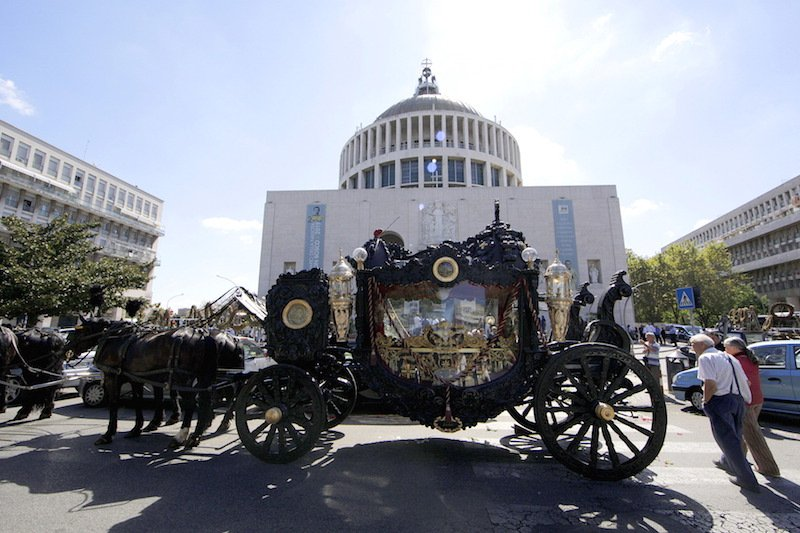 An ornate hearse pulled by six, black-plumed horses, carries the body of Vittorio Casamonicato a Roman Catholic basilica in the Rome suburbs, where a funeral mass was celebrated, August 20, 2015. Casamonica, 65, the head of a notorious Rome crime family, was given a lavish funeral on Thursday, with a helicopter dropping red rose petals on mourners and a brass band playing the theme tune from the Godfather movie. Picture taken August 20, 2015. Photo courtesy REUTERS/Stringer