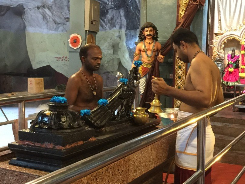 Two holy men perform a ceremony around a peacock god carved of ebony