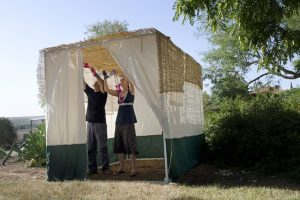 A family decorates a sukkah or makeshift shelter.