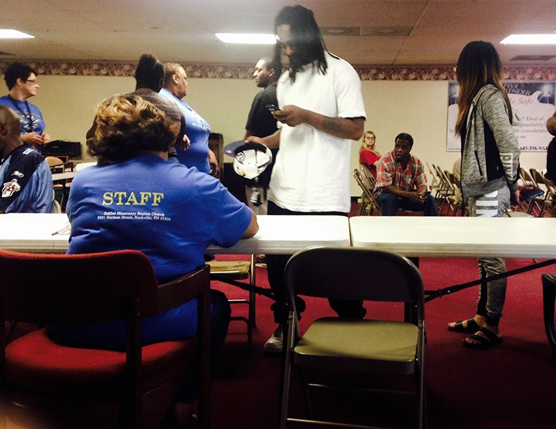 A volunteer assists Fugitive Safe Surrender participants and their accompanying friends and family navigate the program on Sept. 19, 2015, at Galilee Missionary Baptist Church in Nashville, Tenn. Religion News Service photo by Heidi Hall