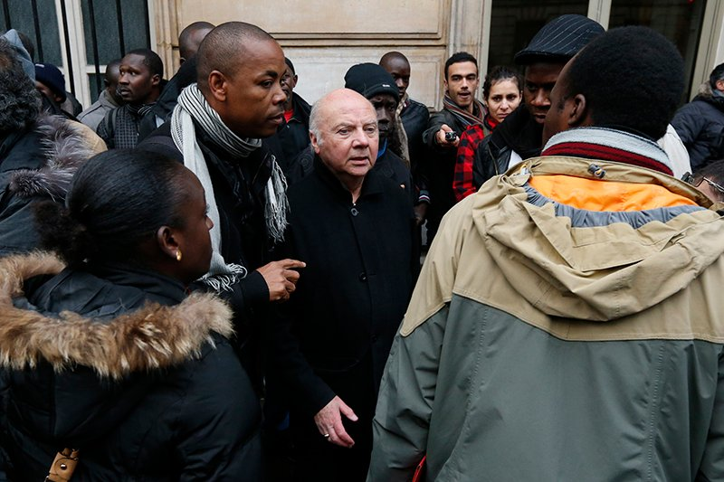 French bishop Jacques Gaillot, center, speaks with people from associations who occupy the rue de Solferino Socialist Party headquarters in Paris on January 3, 2013 in solidarity with illegal immigrants workers who are on hunger strike in Lille, northern France, since 63 days. Photo courtesy of REUTERS/Benoit Tessier