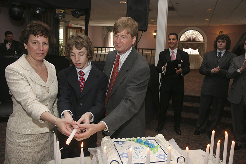 Ari McVeigh, center, lights candles with his parents during his Bar Mitzvah. Photo courtesy of Rod McVeigh