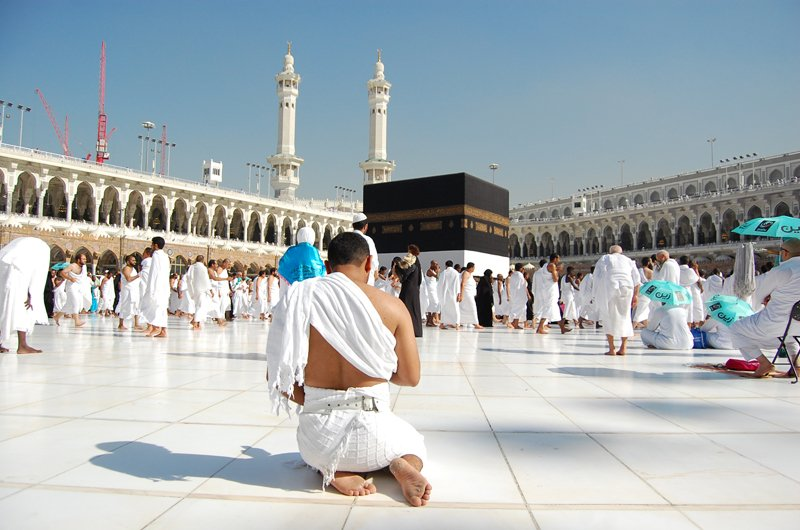 A pilgrim at the Kaaba in Mecca prays alone amongst a sea of the faithful. He sits in the traditional Islamic posture. Photo courtesy of Haram Films, 2015