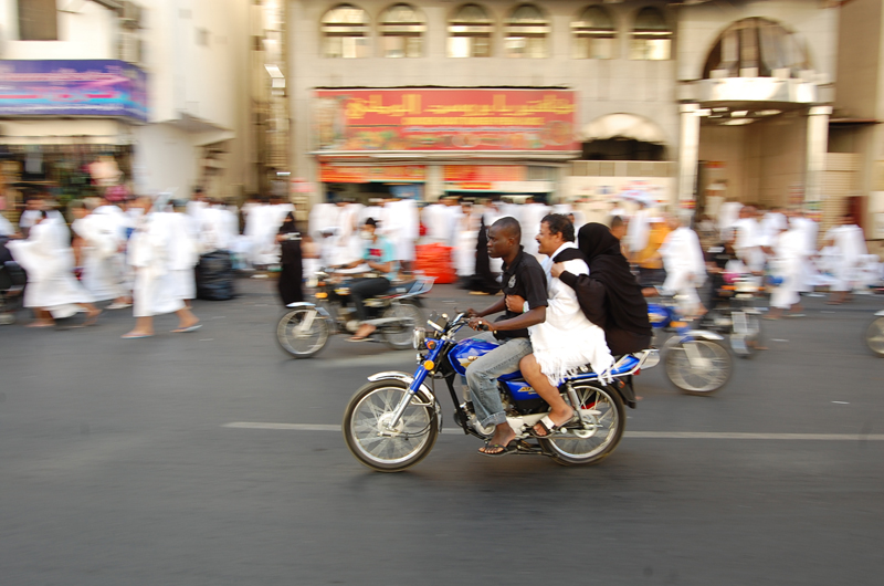 A pilgrim and his wife precariously ride a motorcycle taxi in Mecca on their way to Mina during the Hajj. Photo courtesy of Haram Films, 2015