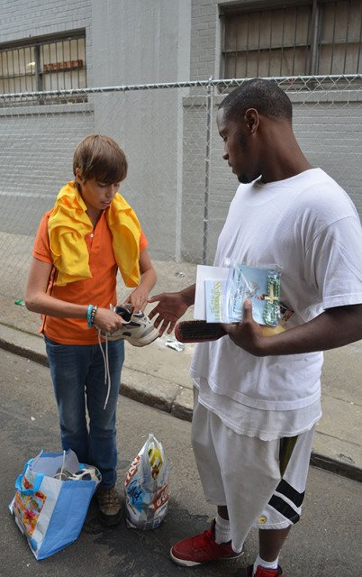 """Simeon Giraldo, left, gives Isaiah Scretching a pair of shoes. Giraldo is participating in a weekend mission trip called """"Serve with Francis,"""" via the Love and Serve ministry, an Atlanta-based group that decided to visit with homeless during Pope Francis' visit to Philadelphia on Sept. 27, 2015. Religion New Service photo by Alex Jacobi"""