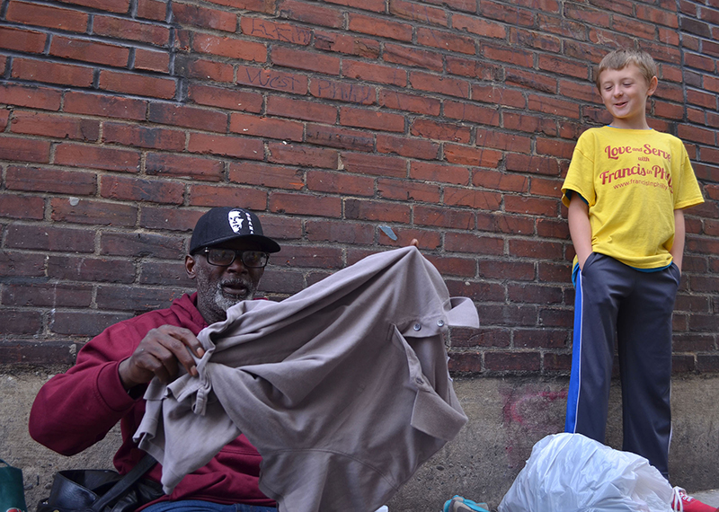 """Melvin White, left, checks out his new shirt, given to him by Lucas Prinke, right, as part of a mission trip with members of the Love and Serve ministry, an Atlanta-based group whose weekend mission trip was dubbed """"Serve with Francis."""" The group decided to visit with homeless during Pope Francis' visit to Philadelphia on Sept. 27, 2015. Religion New Service photo by Alex Jacobi"""