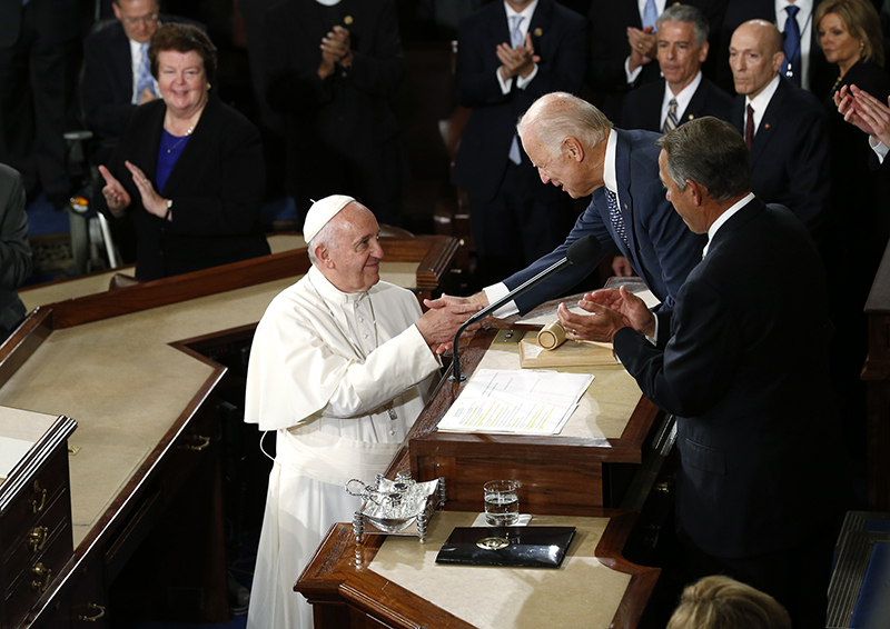 Pope Francis is greeted by U.S. Vice President Joe Biden as the pope arrives in the House Chamber prior to addressing a joint meeting of the U.S. Congress on Capitol Hill in Washington on September 24, 2015. Photo courtesy of REUTERS/Jonathan Ernst *Editors: This photo may only be republished with RNS-POPE-CONGRESS, originally transmitted on Sept. 24, 2015.