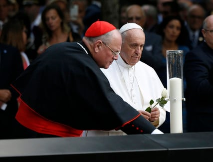 Pope Francis is accompanied by Cardinal Timothy Dolan as he places a flower after praying for the victims at the September 11, 2001 memorial in New York, on September 25, 2015. Photo courtesy of REUTERS/Shannon Stapleton *Editors: This photo may only be republished with RNS-POPE-INTERFAITH, originally transmitted on Sept. 25, 2015.