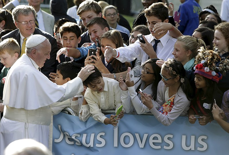 Pope Francis blesses a schoolchild upon departure from the Vatican Embassy in Washington during his first visit to the United States on September 24, 2015. Photo courtesy of REUTERS/Gary Cameron
