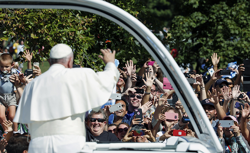 Pope Francis waves from the popemobile during a papal parade in Washington on September 23, 2015. Pope Francis is making his first visit to the United States. Photo courtesy of REUTERS/Pool
