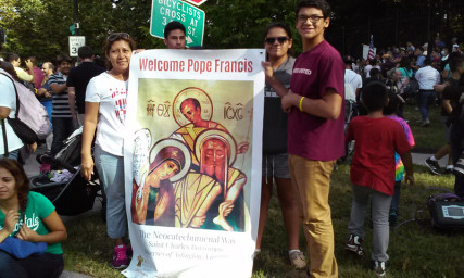 Left to right, Teresa Guzman of Alexandria, Deborah Cornejo, Gabrial Cornejo, both of Herndon, Va., hold a sign welcoming Pope Francis outside the Vatican embassy in Washington, D.C., on Sept. 22, 2015. Religion News Service photo by Adelle M. Banks