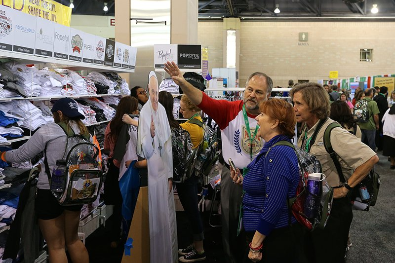 Robert Brock, center, introduces cutomers to his cardboard cutout of Pope Francis on the floor of the convention center at the World Meeting of Families. Photo courtesy of Peter Martin
