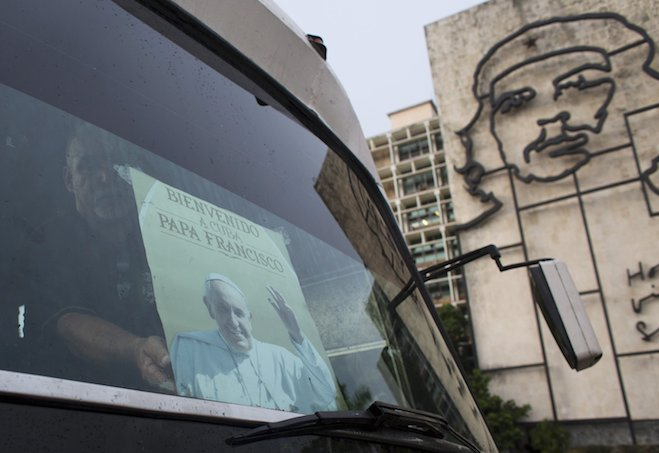 """A Havana bus driver fixes a poster, with an image of Pope Francis and a message reading """"Welcome to Cuba"""", on the windscreen. On right is a bronze sculpture of revolutionary leader Che Guevara. Photo by Alexandre Meneghini courtesy of Reuters."""
