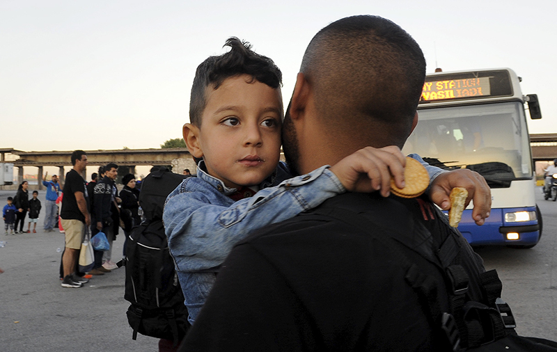 A Syrian refugee boy is carried towards a bus after disembarking a passenger ship at the port of Piraeus, near Athens, Greece, on September 15, 2015. Photo courtesy of REUTERS/Michalis Karagiannis *Editors: This photo may only be republished with RNS-REFUGEES-JEWS, originally transmitted on September 15, 2015.