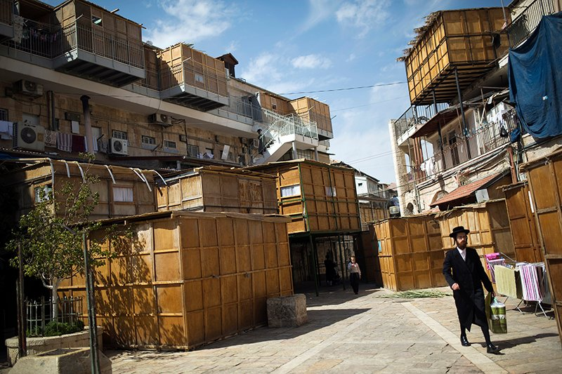 Ultra-Orthodox Jewish men walk near ritual booths, known as sukkot, in Jerusalem's Mea Shearim neighbourhood on October 8, 2014. Photo courtesy of REUTERS/ Amir Cohen *Editors: This photo may only be republished with RNS-SUKKOT-'SPLAINER, originally transmitted on Sept. 29, 2015.