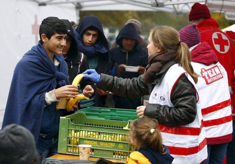 Migrants recieve bananas, soup, bread and tea before crossing the Austrian-German border in Achleiten, Austria, across from Passau, Germany, October 29, 2015. Photo courtesy REUTERS/Michaela Rehle