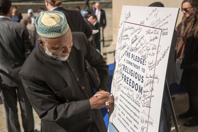Imam Talib Shareef, president of Masjid Muhammad in Washington, D.C., signs a pledge to denounce bigotry and defend religious freedom at a ceremony outside Washington National Cathedral on Oct. 23, 2015. Photo courtesy Danielle Thomas/Washington National Cathedral
