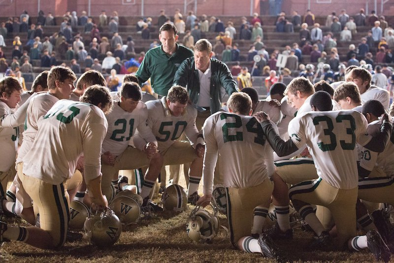 The Woodlawn High School football team, led by defensive coordinator Jerry Stearns (Kevin Sizemore, center left) and head coach Tandy Gerelds (Nic Bishop), pause to pray before an important game in 'Woodlawn.' Photo courtesy Alan Markfield