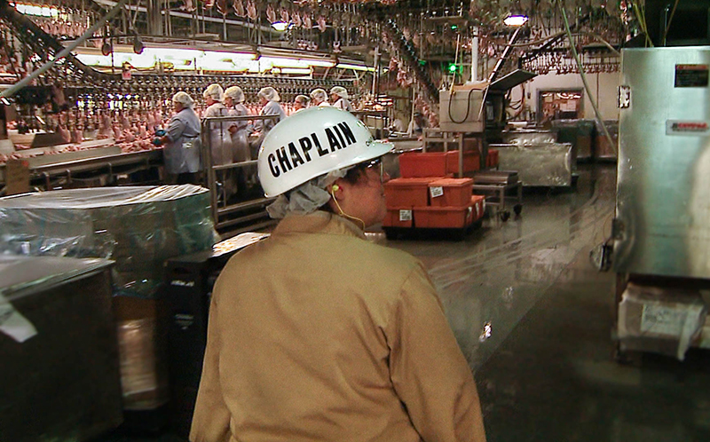 Tyson Foods Chaplain Melissa Brannan walks the production line at a food processing plant in Springdale, Arkansas. Photo courtesy of Journey Films