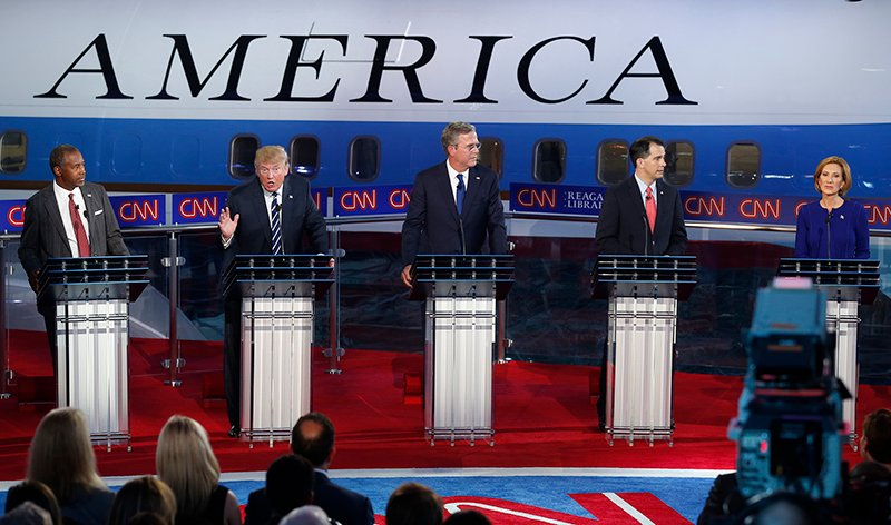 Republican U.S. presidential candidate Dr. Ben Carson, left, watches businessman Donald Trump, second left, criticize the business record of former HP CEO Carly Fiorina, far right, as former Florida Governor Jeb Bush, center, and Wisconsin Governor Scott Walker look over to Fiorina during the second official Republican presidential candidates debate of the 2016 U.S. presidential campaign at the Ronald Reagan Presidential Library in Simi Valley, California, United States, on September 16, 2015. Photo courtesy of REUTERS/Lucy Nicholson