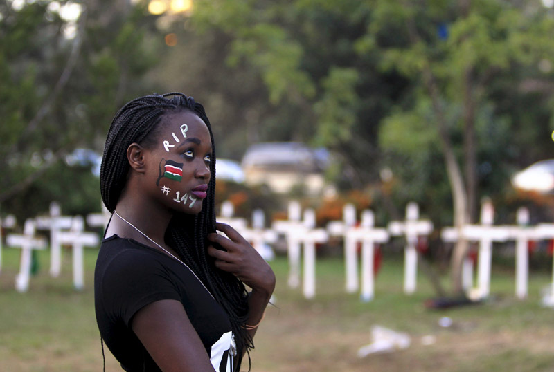 "A student wearing facepaint walks past wooden crosses in memory of the Garissa university students who were killed by gunmen, at a memorial concert at the ""Freedom Corner"" in Kenya's capital Nairobi on April 14, 2015. Photo courtesy of REUTERS/Noor Khamis *Editors: This photo may only be republished with RNS-KENYA-SHABAAB, originally transmitted on Oct. 26, 2015."