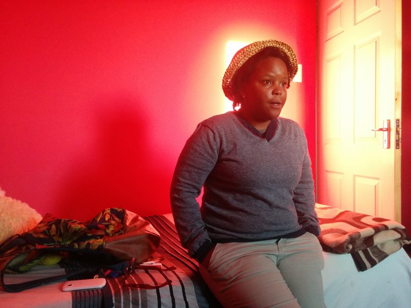 Hlubi George sits on her bed at the iThemba Lam Center in Manenberg, South Africa on October 6, 2015. Religion News Service photo by Brian Pellot.