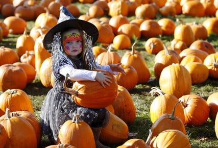 Dressed as a witch, Maisy Thompson plays with pumpkins in the pumpkin patch ahead of Halloween at Crockford Bridge Farm at Addlestone near Woking, southern Britain on October 26, 2015. Photo courtesy of REUTERS/Luke MacGregor *Editors: This photo may only be republished with RNS-SPLAINER-WITCH, originally transmitted on Oct. 27, 2015.