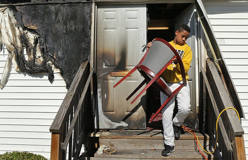 Tony McMiller, 13, helps carry chairs outside on Sunday, Oct. 18, 2015, at the New Life Missionary Baptist Church in St. Louis, so that parishioners could sit in the yard. The church was damaged by an arson fire on Saturday, Oct. 17, 2015, so the service was held outside. Photo by J.B. Forbes, courtesy of St. Louis Post-Dispatch
