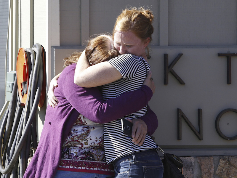 Umpqua Community College alumnus Donice Smith (L) is embraced after she said one of her former teachers was shot dead, near the site of a mass shooting at Umpqua Community College in Roseburg,Oregon October 1, 2015. Photo courtesy REUTERS/Steve Dipaola