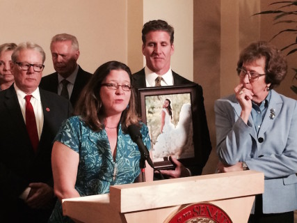 Toni Broaddus, at the microphone, is California campaign director for Compassion & Choices. She is with Dan Diaz, the husband of the late Brittany Maynard who is pictured in her wedding gown, and legislators who sponsored the bill to legalize physician assisted dying, Senate Majority leader Bill Monning on the left and Senate majority whip Lois Wolk on the right. Photo courtesy of Compassion & Choices