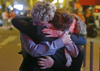 People hug on the street near the Bataclan concert hall following fatal attacks in Paris, France, November 14, 2015. Gunmen and bombers attacked busy restaurants, bars and a concert hall at locations around Paris on Friday evening, killing dozens of people in what a shaken French President described as an unprecedented terrorist attack. REUTERS/Christian Hartmann - RTS6X48