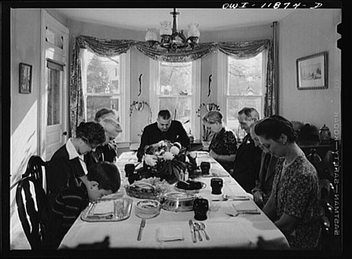 A family says grace before Thanksgiving dinner at the home of Earle Landis (1942).
