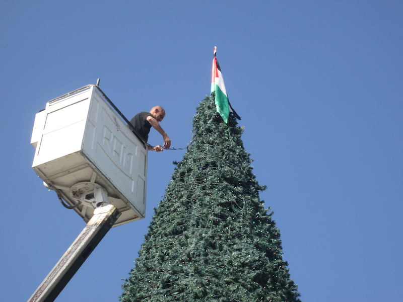 A worker wraps festive lights around a tall Christmas tree in Bethlehem topped by a Palestinian flag. RNS photo by Michele Chabin