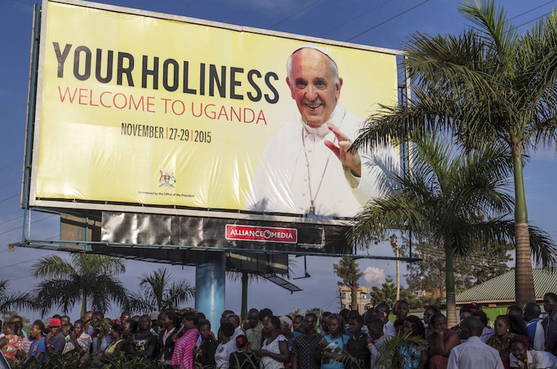 Ugandans wait along the road as for the arrival of Pope Francis along the streets of the capital Kampala, November 27, 2015. Photo courtesy REUTERS/Edward Echwalu