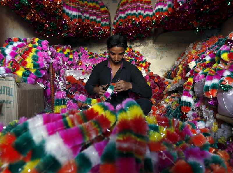 A vendor makes artificial garlands for sale inside his shop ahead of the Hindu festival of Diwali in Ahmedabad, India, on October 29, 2015. Flowers are offered to Hindu gods and goddesses on the occasion of Diwali, the annual festival of lights that will be celebrated across the country on November 11. Photo courtesy of REUTERS/Amit Dave *Editors: This photo may only be republished with RNS-MENON-COLUMN, originally transmitted on Nov. 9, 2015.