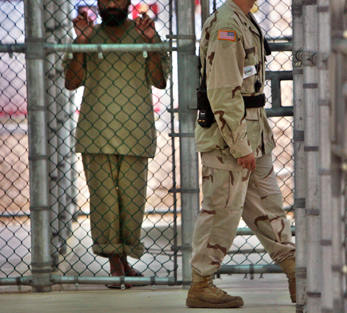 In this photo reviewed by U.S. military officials, a detainee whose name, nationality, and facial identification are not permitted, holds onto a fence as a U.S. military guard walks past the grounds of the maximum security prison at Camp 5 in the Guantanamo Bay U.S. Naval Base on June 26, 2006. Photo courtesy of REUTERS