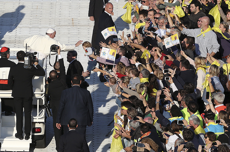 Pope Francis blesses a baby as he arrives to celebrate a mass at the Artemio Franchi stadium during his pastoral visit in Florence on November 10, 2015. Photo courtesy of REUTERS/Stefano Rellandini