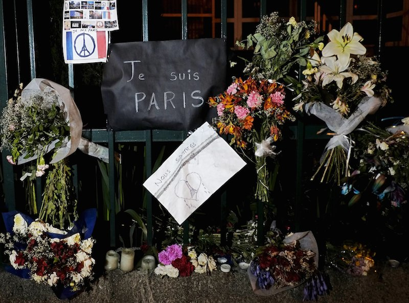 Flowers and banners are pictured, as a tribute to the victims of Paris attacks at the gate of French embassy in La Paz, Bolivia November 18, 2015. Photo by David Mercado, courtesy of Reuters