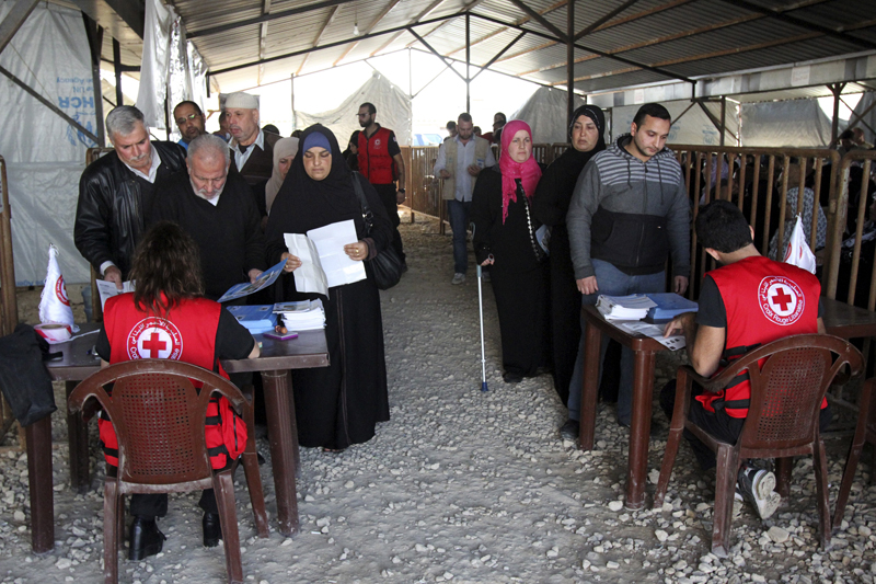Syrian refugees line up to receive aid for the winter from the UN refugee agency (UNHCR) in Tripoli, northern Lebanon on November 18, 2015. Photo courtesy of REUTERS/Omar Ibrahim *Editors: This photo may only be republished with RNS-REFUGEE-RESETTLE, originally transmitted on Nov. 19, 2015.