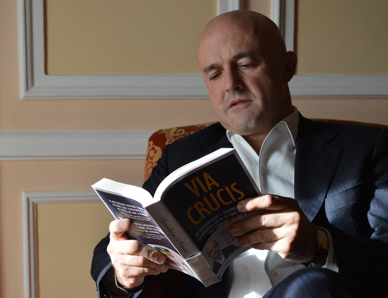 """Italian author Gianluigi Nuzzi holds an Italian copy of his new book, """"Merchants in the Temple,"""" in Rome on Nov. 5, 2015. Religion News Service photo by Rosie Scammell"""