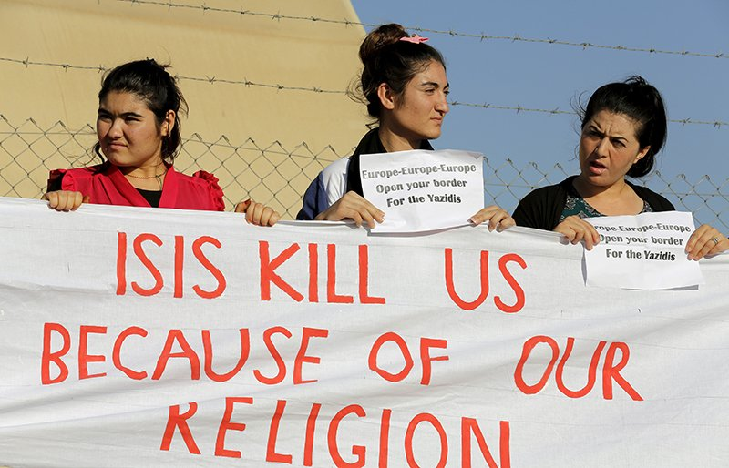 Islamic State documents seized by U.S. forces reveal religious rulings justifying slavery, rape and pillage of antiquities. Yazidi refugee women protest their treatment. Photo courtesy of REUTERS/Umit Bektas