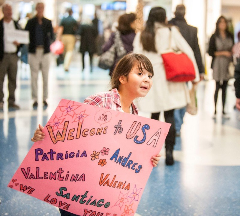 Girl welcomes refugee family arriving at the airport. Courtesy USCCB/Sarah Williamson.