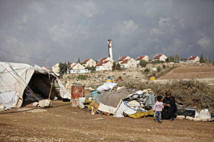 Hebron region. In the foreground, a tent where a Palestinian family lives, and in the background an illegal Israeli settlement. - Courtesy of the ICRC of the Red Cross (http://bit.ly/1jQzK9r)