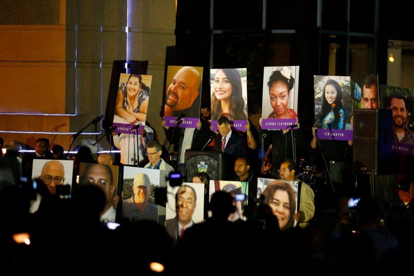 People hold photos of the mass shooting victims during a moment of silence at a vigil in San Bernardino, California December 7, 2015. Photo by Mike Blake, courtesy of REUTERS.
