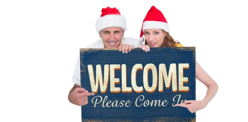 Couple holds a Welcome sign.