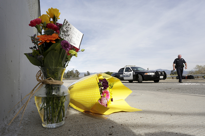 A San Bernardino police officer stands near flowers left near the scene of Wedneday's shooting rampage, at the Inland Regional Center, in San Bernardino, California on December 3, 2015. Photo courtesy of REUTERS/Jonathan Alcorn